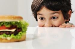 Niño mirando una hamburguesa
