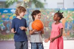 Niños jugando con una pelota de baloncesto